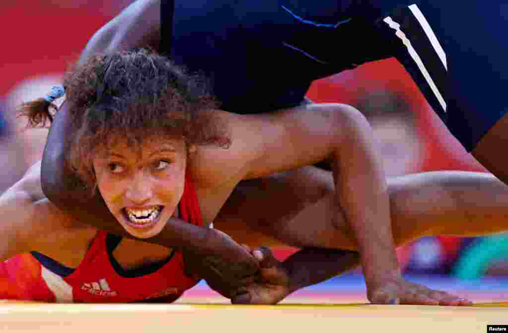 Senegal's Isabelle Sambou (in blue) fights with Tunisia's Maroi Mezien on the repechage of the Women's 48Kg Greco-Roman wrestling.