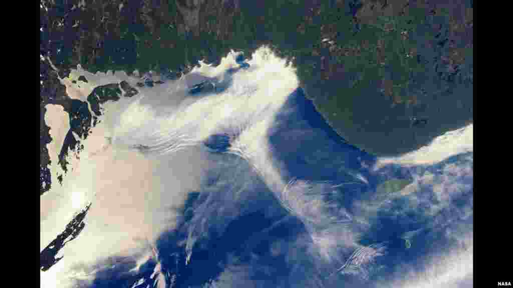 From the vantage point of the International Space Station, astronauts frequently observe atmospheric and surface phenomena in ways that are impossible to view from the ground. Two such phenomena - gravity waves and sunglint - are illustrated in this photograph of northeastern Lake Superior.