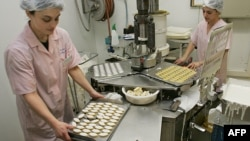 FILE - Two employees prepare 'calissons,' a traditional French candy, in Aix-en-Provence, southern France, Dec. 14, 2005.