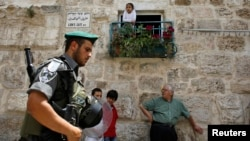 Israeli border police officer walks past Palestinians in Jerusalem's Old City before a parade marking Jerusalem Day, May 8, 2013.