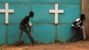 "People hide from gunfire near church during firefight between African peacekeepers, fighters from the Christian ""anti-balaka"" militia, Bangui, Feb. 18, 2014."