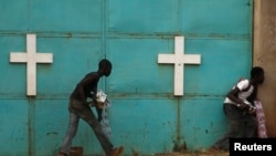 """People hide from gunfire near church during firefight between African peacekeepers, fighters from the Christian """"anti-balaka"""" militia, Bangui, Feb. 18, 2014."""