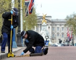 Metropolitan police officers carry out security checks on drains and lamp posts along the Mall ahead of the Royal wedding in London, April 26, 2011