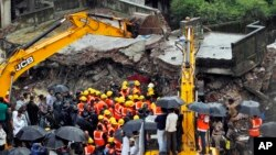 Indian rescue workers look for trapped people after a residential building collapsed in Thane district on the outskirts of Mumbai, India, June 21, 2013.