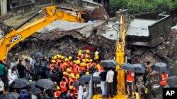 Nhân viên cứu hộ Ấn Độ tìm kiếm người bị mắc kẹt trong tòa nhà bị sập đổ ở ngoại ô Mumbai, ngày 21/6/2013.