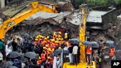 Tim SAR India melakukan upaya pencarian korban yang terperangkap dalam reruntuhan gedung apartemen yang rubuh di wilayah Thane, pinggir kota Mumbai, India (21/6).