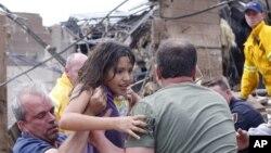 Seorang anak ditarik dari reruntuhan Sekolah Dasar Plaza Towers di Moore, Oklahoma (20/5) menyusul tornado yang menghantam negara bagian itu. (AP/Sue Ogrocki)