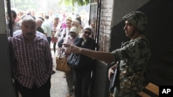 An Egyptian soldier directs a voter inside a polling station June 16, 2012 in Cairo, Egypt.