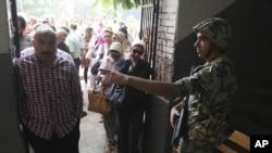 Binh sĩ Ai Cập hướng dẫn cử tri bên trong một trạm bỏ phiếu tại Cairo, ngày 16/6/2012