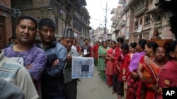 FILE - Nepalese stand in line to vote at a polling station in Bhaktapur, Nepal, May 14, 2017. Nepalese lined up to vote for representatives in municipality and village council positions held in the Himalayan nation for the first time in two decades.