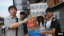 示威人士黃同學(左一)焚燒中共黨旗,抗議中國干預香港事務