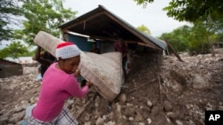 Residents salvage a mattress from a home partly submerged in mud from a mudslide triggered by Tropical Storm Erika in Montrouis, Haiti, Aug. 29, 2015.