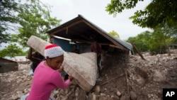 海地居民们打捞因热带风暴艾瑞卡而深陷泥潭的床垫(2015年8月29日)。
