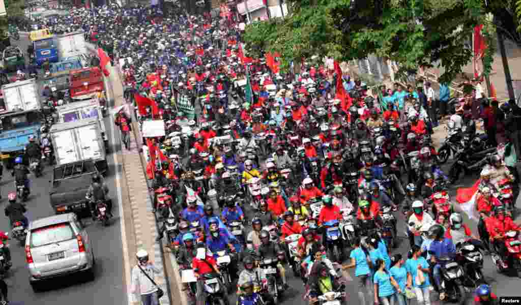 Workers ride their motorcycles along a street during a demonstration in an industrial area of Tangerang, on the outskirts of Jakarta, Oct. 3, 2012.