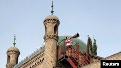 Seorang imam dari kelompok Muslim Uighur di Xinjiang, China, melakukan azan. (Foto: Dok)