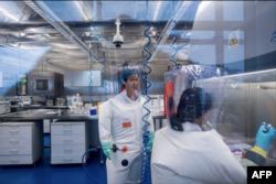 资料照:武汉病毒研究所的病毒学家石正丽(左)在该所的P4实验室内。