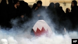 A Bahraini anti-government protester wearing a national flag gets up after falling when riot police fired tear gas at a mourning procession on Nov. 13, for a teenager whose death the opposition blames on police