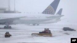 14일 폭설이 내린 미국 뉴저지주 뉴워크 리버티 국제공항에서 직원들이 제설작업을 하고 있다. 뒤로 운항이 취소된 항공기들이 서 있다.