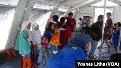 Para Relawan dari Komunitas Pecinta Alam Malang Satu Jiwa, Jawa Timur saat membawakan sesi pelajaran gempa bumi melalui permainan dan nyanyian di tenda kelas darurat Sekolah Dasar Negeri Lolu, Kabupaten Sigi, Sulawesi Tengah, Kamis, 25 Oktober 2018. (Foto: VOA/Yoanes Litha).