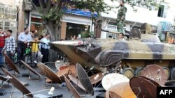 FILE- Iranian soldiers destroying satellite dishes with an army tank in the southwestern city of Shiraz. Iranian authorities carry out regular crackdowns to remove satellites from rooftops, and issue warnings against their use, Sept. 28, 2013.