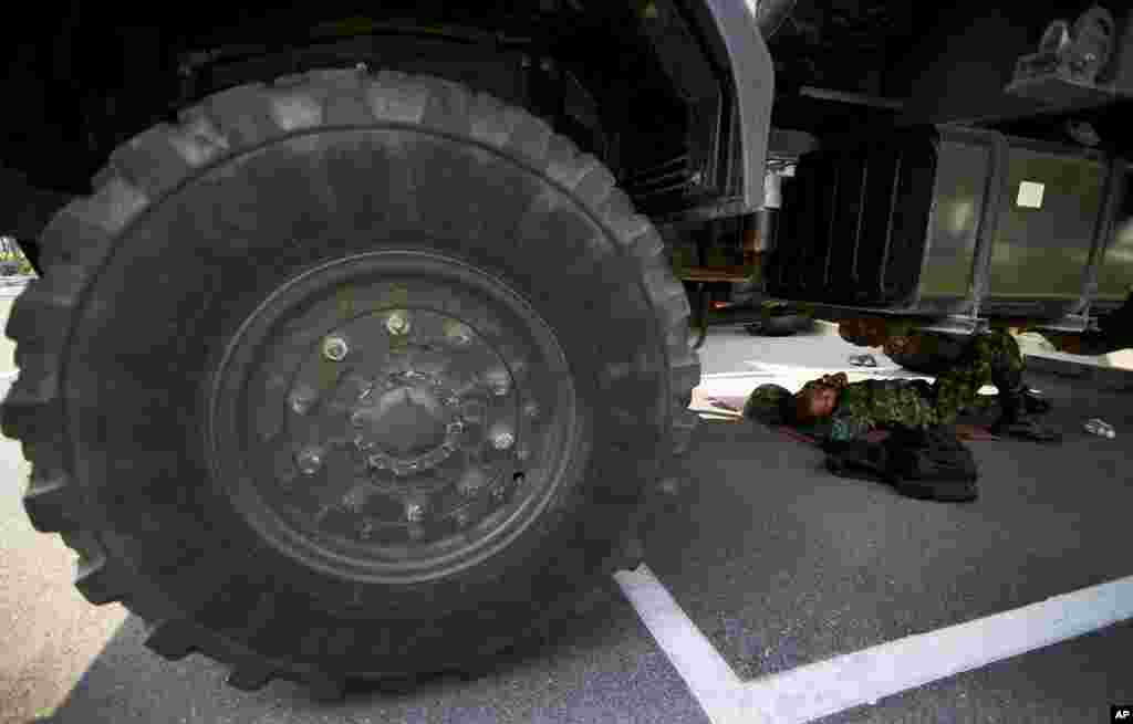A Thai soldier lies under a truck to take a nap at National Anti-Corruption Commission office in Bangkok, Feb. 27, 2014.
