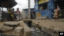 A woman sells food next to an open sewer in the Adjame neighborhood of Abidjan, Ivory Coast, January 28, 2011