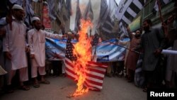 FILE - Supporters of the Jamaat-ud-Dawa Islamic organization burn a mock U.S. flag during a protest in Peshawar, Pakistan, May 27, 2016.