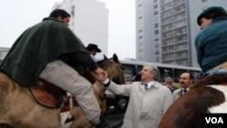 El presidente Tabaré Vázquez saluda a los jinetes que protestaban el traslado de los restos de Artigas.