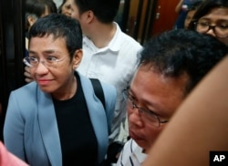 Maria Ressa, the award-winning head of a Philippine online news site Rappler that has aggressively covered President Rodrigo Duterte's policies, is escorted into another room following her arrest by National Bureau of Investigation agents in a libel case,