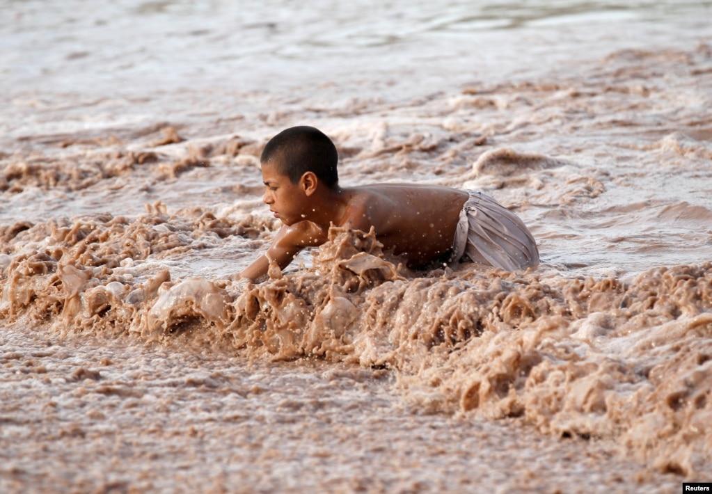 아프가니스탄 잘랄라바드의 진흙탕에서 한 소년이 물장난을 하고 있다.