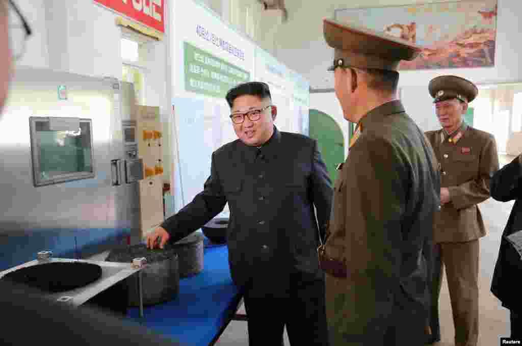 """김정은 북한 국무위원장이 국방과학원 화학재료연구소를 시찰하고 있다. 김 위원장 뒤에 '3D 복합재료뿐 아니라 4D(복합재료도) 빨리 개발하여야 한다""""는 자신의 발언 자료가 벽면에 붙어 있다."""