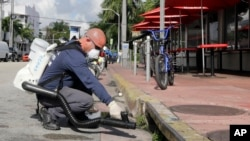 Petugas menyemprot bahan kimia ke dalam saluran pembuangan di Pantai Miami, Florida, dalam upaya melawan virus Zika (23/8). (AP/Alan Diaz)