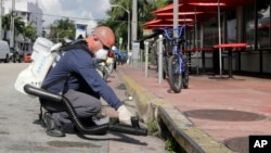 """Miami-Dade mosquito control inspector Yasser """"Jazz"""" Compagines sprays a chemical mist into a storm drain, Tuesday, Aug. 23, 2016, in Miami Beach, Florida. Governor Rick Scott has announced that the Florida Department of Health is adding another $5 million in funding to Miami-Dade County for Zika preparedness and mosquito control. (AP Photo/Alan Diaz)"""