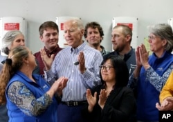 FILE - Former vice president and Democratic presidential candidate Joe Biden, center, is applauded as he speaks during a tour at the Plymouth Area Renewable Energy Initiative in Plymouth, N.H., June 4, 2019.