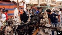 Civili razgledaju ostatke automobila-bombe koji je eksplodirao juče, u jednoj od šiitskih oblasti Bagdada