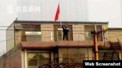 网上流传的贾敬龙家被拆时的照片,贾敬龙举红旗站在楼上