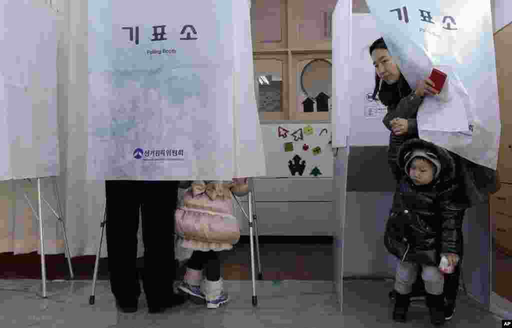 A South Korean woman with her son, tries to come out from a booth at a polling station in Seoul, Dec. 19, 2012.