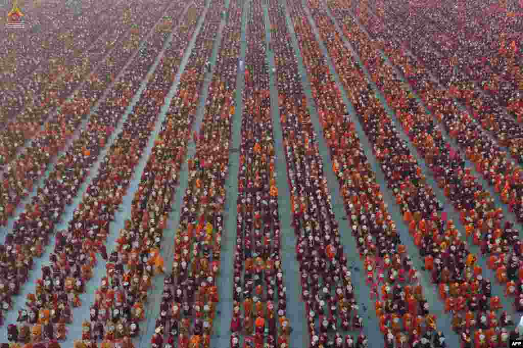 A handout photo released by Dhammakaya Fondation shows monks lining up for alms during the alms-giving ceremony to 30,000 monks organized by the regional government of Mandalay affiliated with Dhammakaya Foundation at Chanmyatha Airport in Mandalay, Myanmar.
