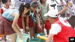 지난 2012년 북한 평안남도 안주시에서 폭우로 수해를 입은 주민들이 국제기구에서 제공한 식수를 배급받고 있다. (자료사진)