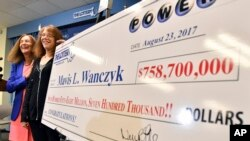 Mavis Wanczyk, of Chicopee, Mass., stands by a poster of her winnings during a news conference where she claimed the $758.7 million Powerball prize at Massachusetts State Lottery headquarters, Aug. 24, 2017, in Braintree, Mass.