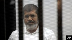 FILE - Egypt's ousted Islamist President Mohamed Morsi sits in the defendant cage in the Police Academy courthouse during a court hearing on charges of inciting the murder of his opponents, in Cairo, Egypt, Nov. 3, 2014.