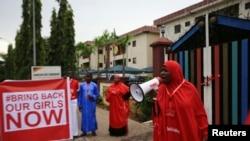 """Seseorang melakukan kampanye """"#Bring Back Our Girls"""" dan meneriakkan slogan selama rally dan menuntut pembebasan murid perempuan yang diculik pada bulan April oleh militan Boko Haram, di Abuja, 17 Oktober 2014."""