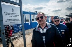 FILE - Hungarian Interior Minister Sandor Pinter, foreground, inspects the enlarged transit zone set up for migrants at the country's southern border with Serbia near Tompa, 169 kms southeast of Budapest, April 6, 2017.