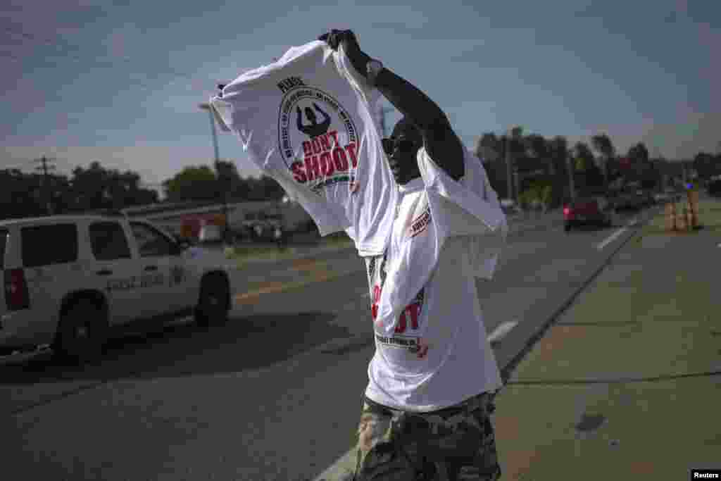 A man sells T-shirts along the roadside in Ferguson, Missouri, Aug. 21, 2014.