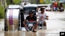People travel through a flooded road brought about by Typhoon Mangkhut, which hit the northern Philippines on Saturday. (AP Photo/Bullit Marquez)