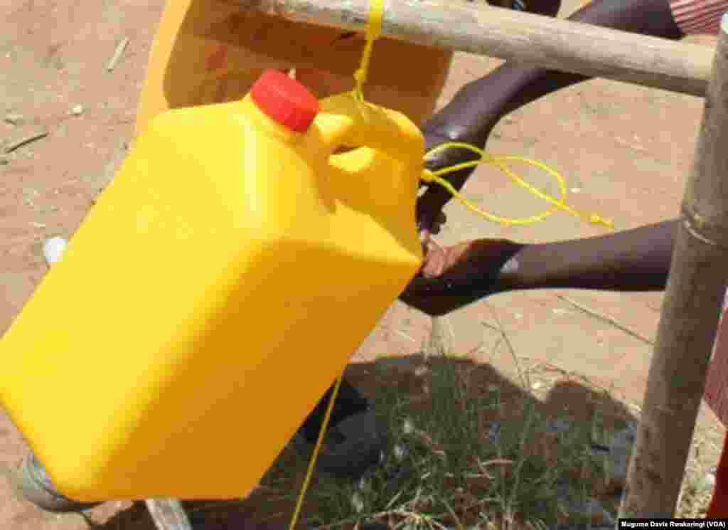 South Sudanese kids wash their hands using water from a jerry can.