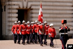 Canadian Captain Megan Couto, second right, makes history by becoming the first female Captain of the Queen's Guard as she takes part in the Changing the Guard ceremony at Buckingham Palace in London, Monday, June 26, 2017.