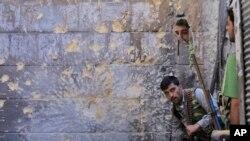 在叙利亚阿勒颇市,一名自由叙利亚军战士利用镜子来观察政府军的动向。(2012年9月24日)