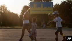 "People walk past a sign that reads ""Kramatorsk is Ukraine!"" painted in colors of Ukrainian national flag, in Kramatorsk, eastern Ukraine, Aug. 9, 2014."
