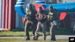 Terrorist Mounir al-Motassadeq is led from one helipcopter to another at the airport in Hamburg, northern Germany, Oct. 15, 2018.